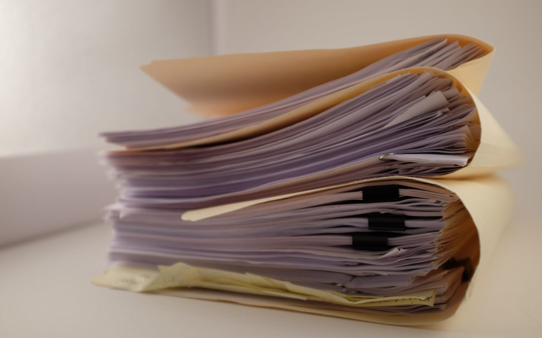 A stack of folders, contracts, papers